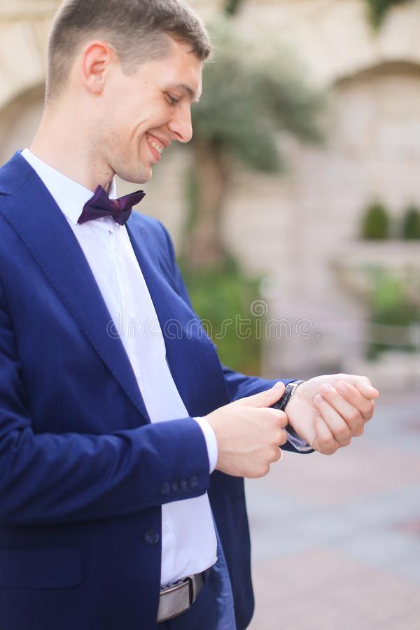 Happy smiling groom waiting for bridea and looking at watch. royalty free stock photo