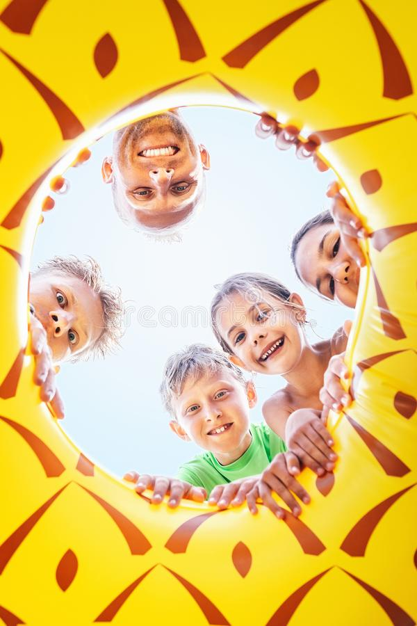 Happy smiling group of childs, teens and adult people look down. Into the inflatable ring hole royalty free stock photos