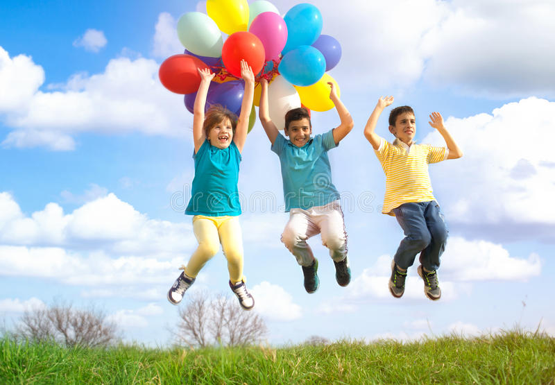 Happy smiling group of kids jumping with balloons on a green meadow. Happy childs playing with colorful toy balloons outdoors royalty free stock images