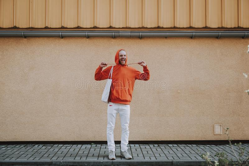 Happy smiling hipster man having fun on walk. Urban lifestyle concept. Full length portrait of young joyful hipster man in red fleece having fun with its hood stock image