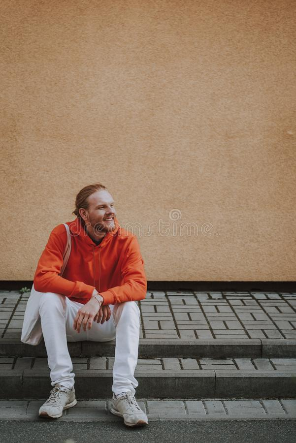 Happy smiling hipster man sitting on stairs. Urban lifestyle concept. Full length portrait of young joyful hipster man in red fleece sitting on stairs near royalty free stock photos