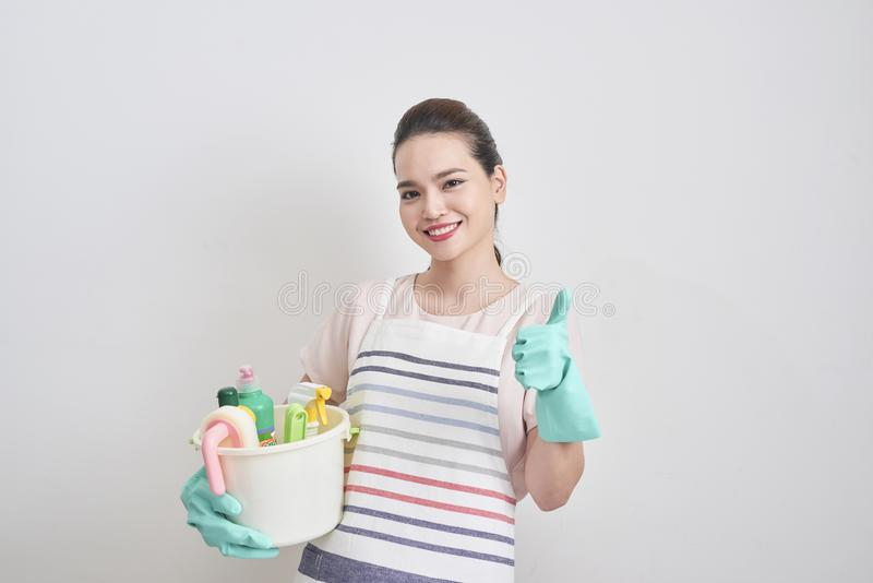 Happy smiling housewife holding cleaning tools and showing thumb stock photo