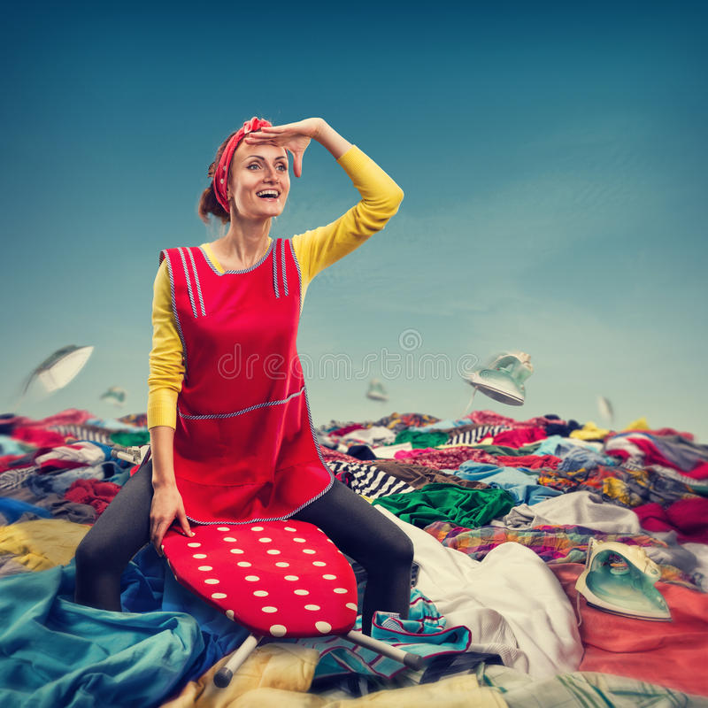Happy smiling housewife surfing on ironing-board. Happy smiling housewife sitting on ironing-board on clother stock images