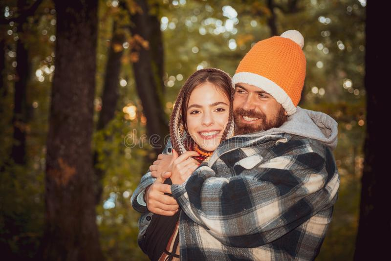 Happy smiling and hugging couple in warm knitted hat and scarf walking outdoor in autumn forest. Cozy mood and autumn stock image