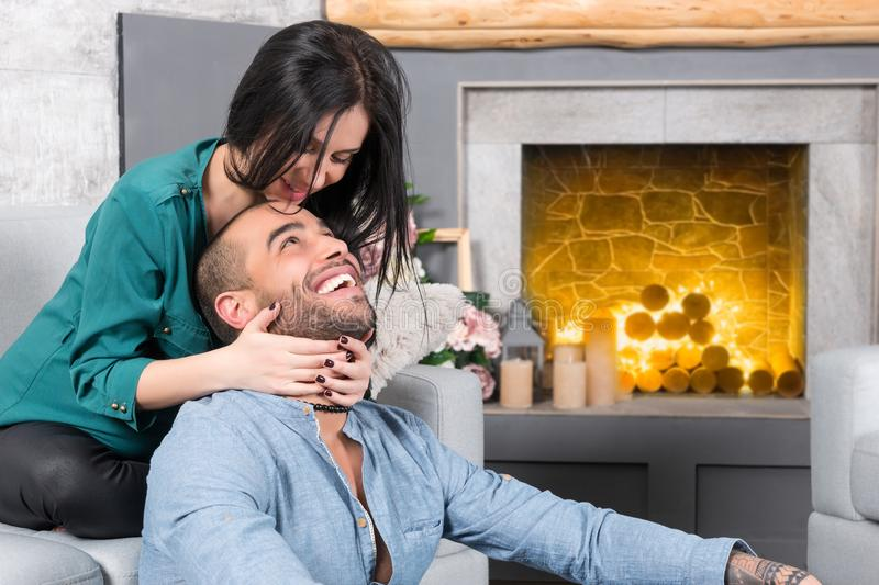 Happy smiling international couple of man with beard and his brunette pregnant wife sitting on the sofa and hugging him royalty free stock photos
