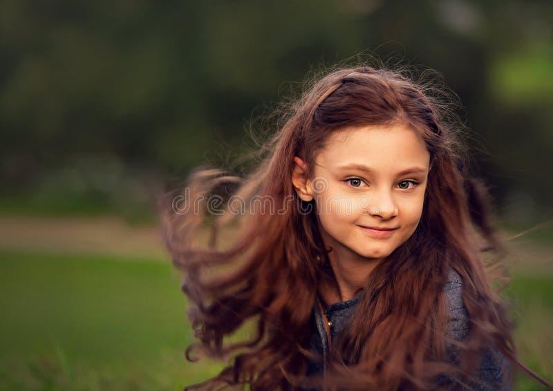 Happy smiling kid girl waving long hair on summer green grass background. Closeup stock photo