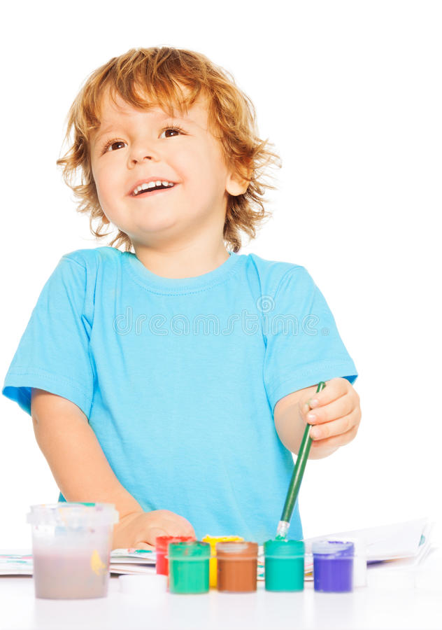 Happy shy kid painting. Happy smiling kid painting with paintbrush and colorful vivid colors, smiling, isolated on white stock images