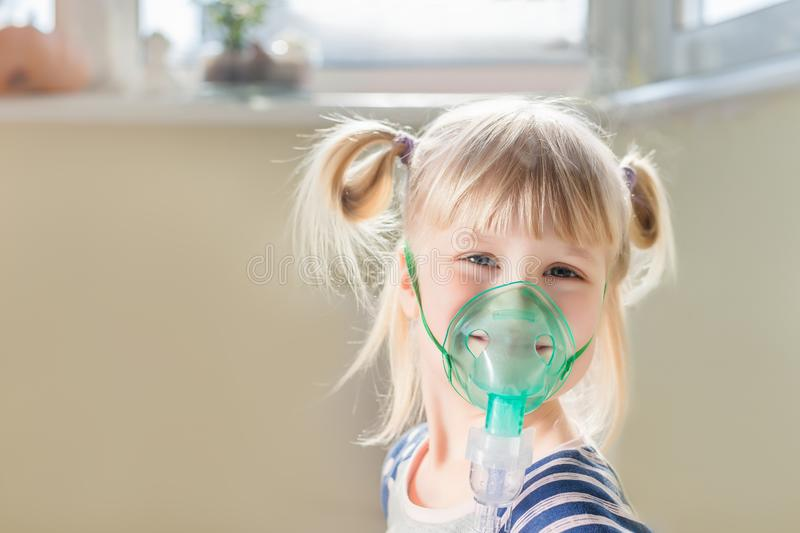 Happy smiling kid using nebuliser mask. Inhalation therapy curing chest cold and coughing. Healthcare and disease prevention conce royalty free stock photos