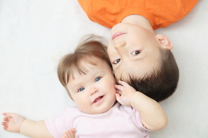 Happy smiling kids, portrait of boy and baby girl looking at each other, happiness in childhood of siblings royalty free stock images