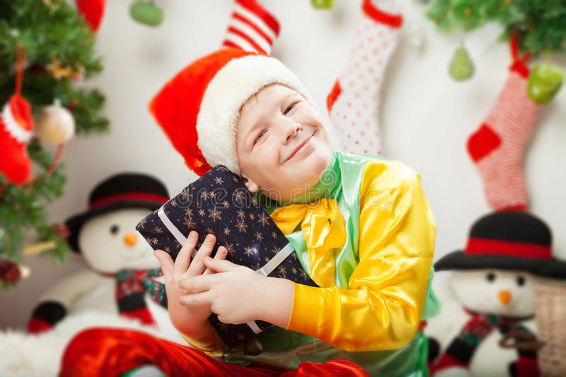 Happy smiling little boy with christmas gift boxes royalty free stock image