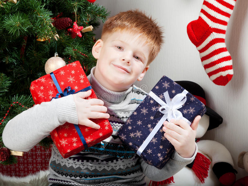 Happy smiling little boy with christmas gift boxes royalty free stock photo