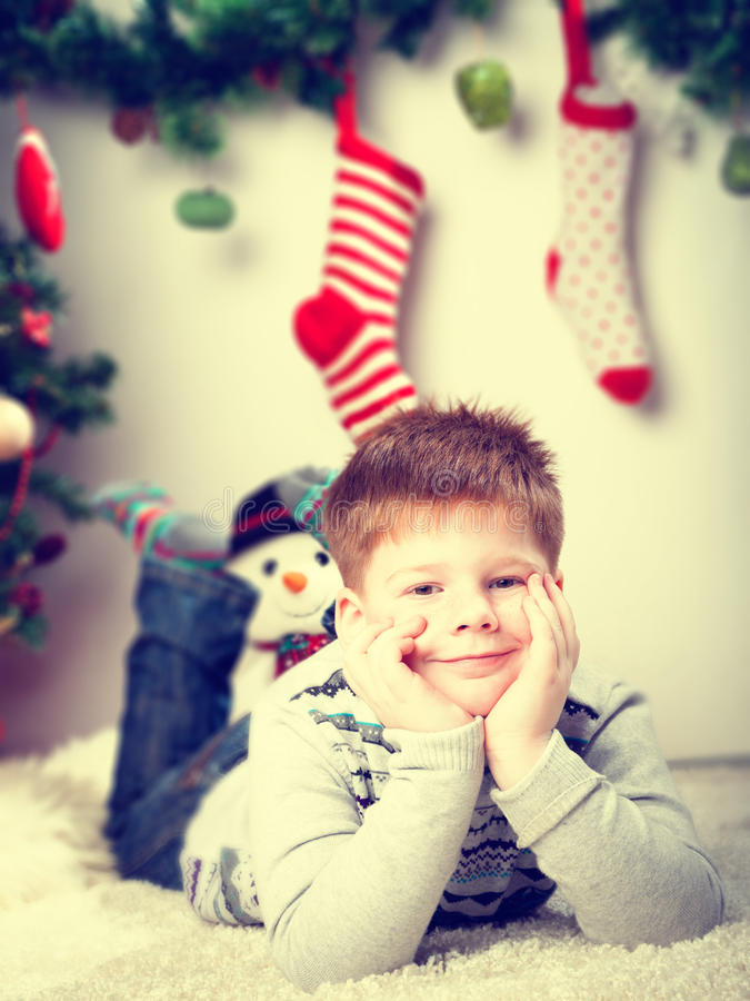 Happy smiling little boy near the Christmas tree royalty free stock photography