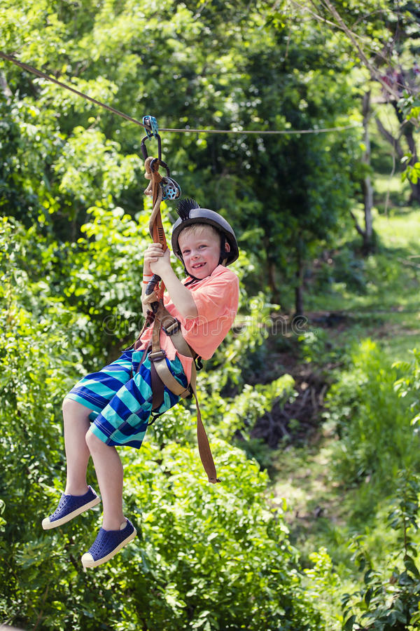 Happy smiling little boy riding a zip line in a lush tropical forest. While on family vacation stock image