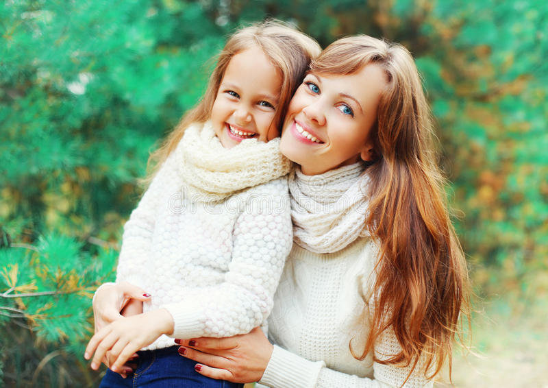 Happy smiling little girl child and mother in winter over tree stock image