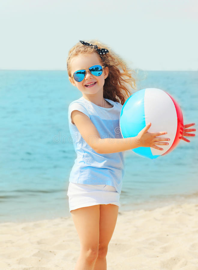 Happy smiling little girl child playing with inflatable water ball on beach near sea. Summer royalty free stock image