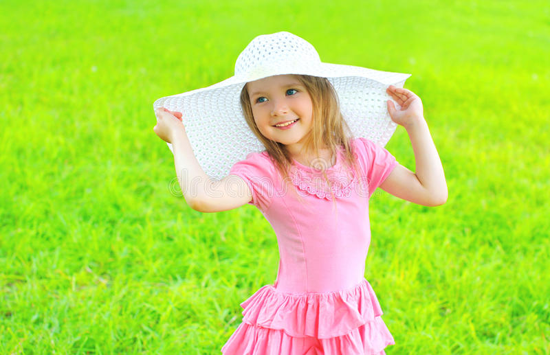 Happy smiling little girl in dress and straw hat outdoors royalty free stock images