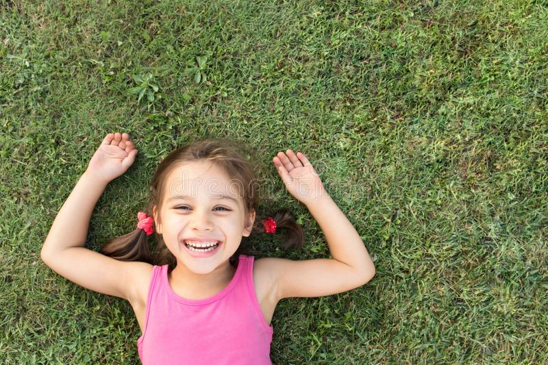 Happy Smiling Little Girl Laying On Grass In Park stock images