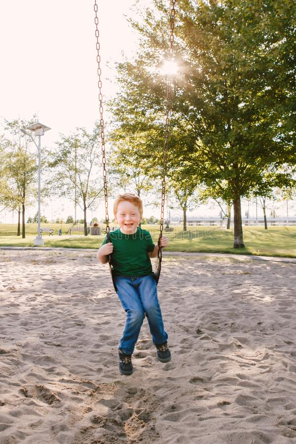 Happy smiling little preschool boy swinging on swingsat playground outside on summer day. Happy childhood lifestyle concept. royalty free stock photos