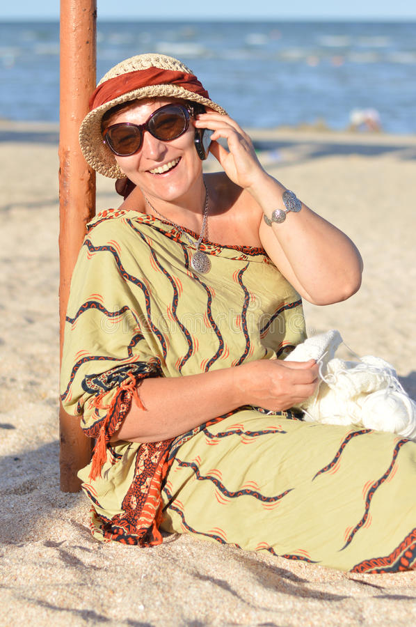 Happy smiling & looking at camera mature woman sitting on beach and talking on mobile phone stock photo