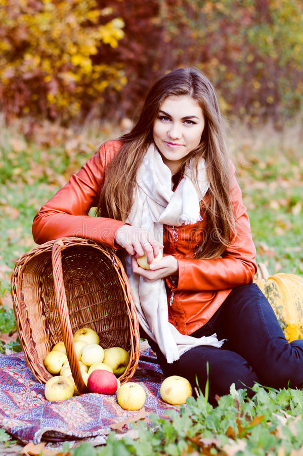 Happy smiling & looking at camera young woman with basket of fresh apples royalty free stock photos