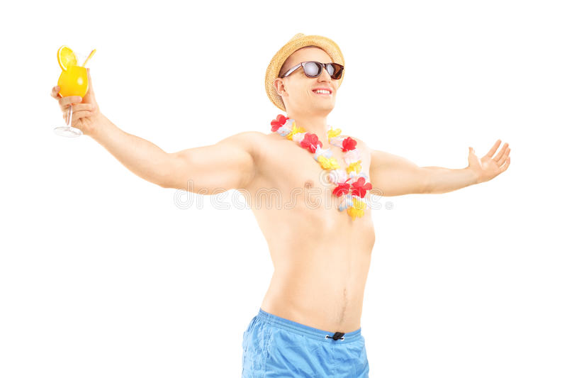 Happy smiling male on a vacation holding a cocktail and spreading his arms stock image