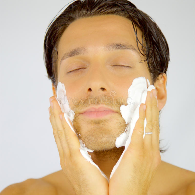 Happy smiling man applying cream on face before shaving royalty free stock photography