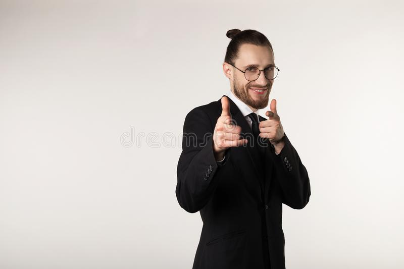 Happy smiling man with beard and trendy hairstyle wearing black suit and glasses looking and pointing at camera royalty free stock photography