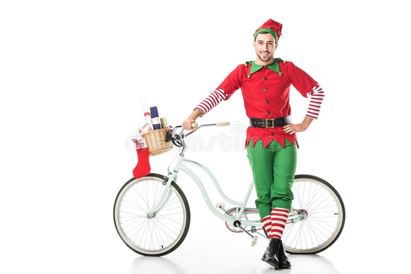 Happy smiling man in christmas elf costume with hand on hip standing near bike with basket full of presents isolated. On white stock images