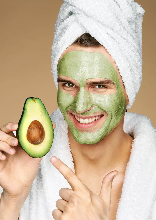 Happy smiling man with facial mask of avocado. stock image