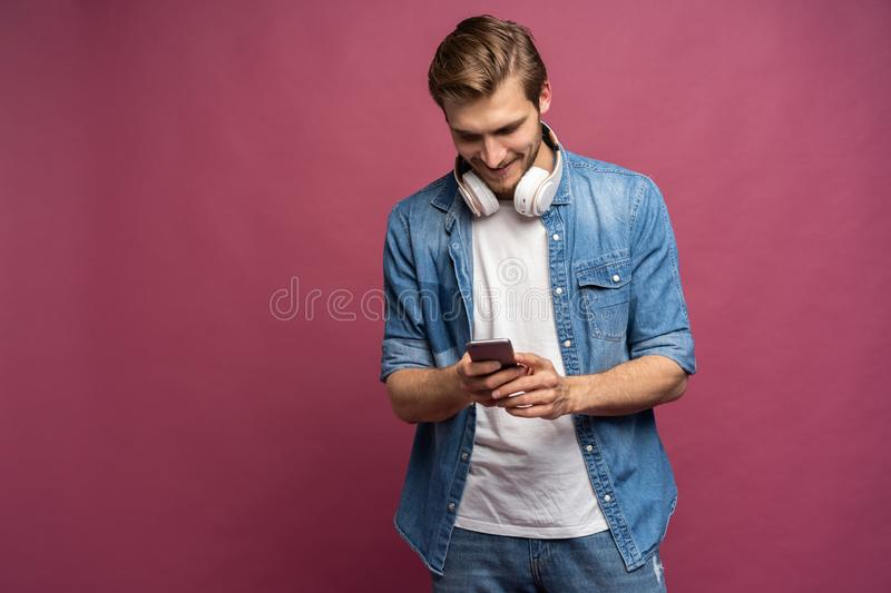Happy smiling man with headphones listening music on his smartphone isolated on pink background. Mobile entertainment lifestyle royalty free stock photos