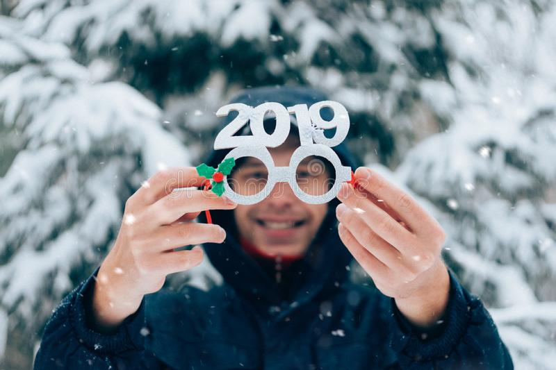 Happy smiling man holding party new year glasses with numbers 2019 in winter park. Christmas outdoor man portrait on winter on the royalty free stock photo