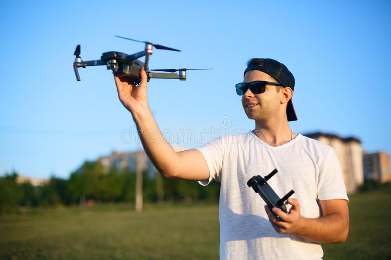 Happy smiling man holds small compact drone and remote controller in his hands. Pilot launches quadcopter from his palm. Drone ready to go on gps stock image