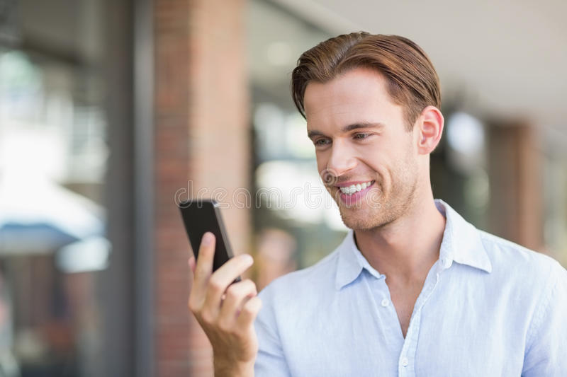 A happy smiling man looking at the phone stock images