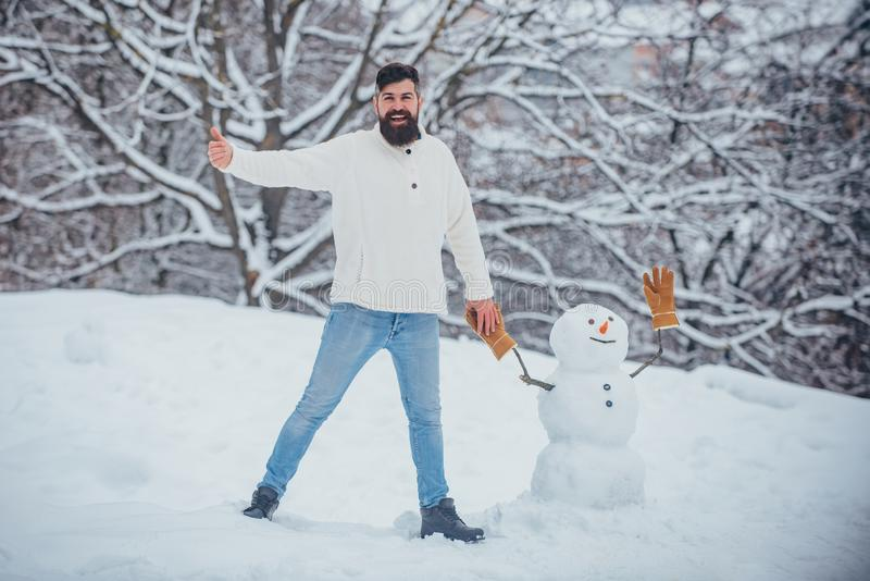 Happy smiling man make snowman on sunny winter day. Winter man. Fashion portrait of young model man indoors with stock photo