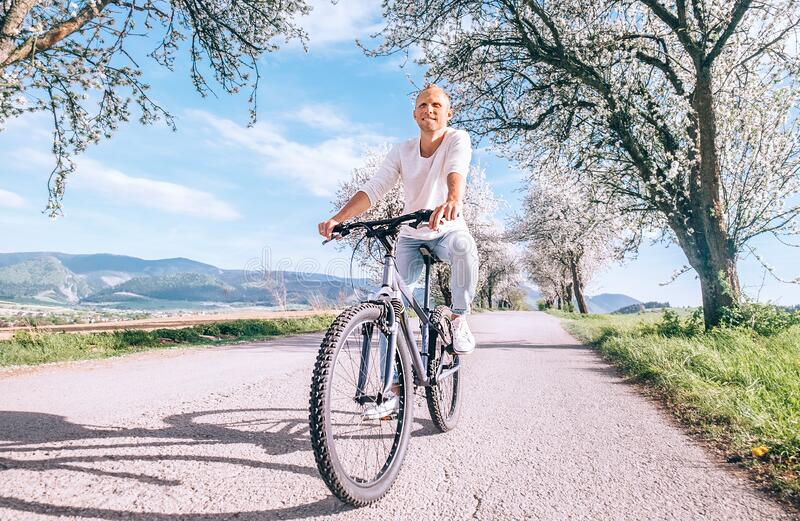Happy smiling man riding a bicycle on the country road under blossom trees. Spring is comming concept image stock image