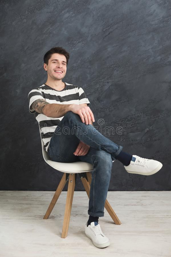Young smiling man sitting at gray studio background stock image