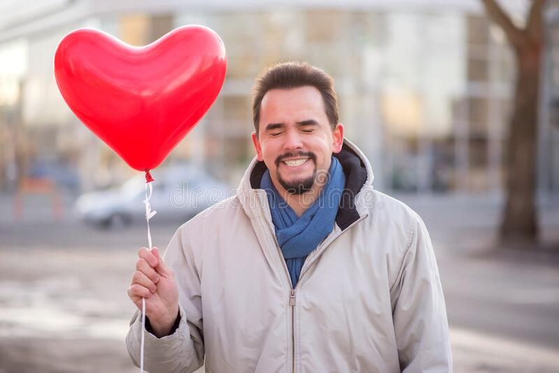 Happy smiling man standing with closed eyes and holding with  red heart-shaped air balloon. Date and Valentines day concept. Portrait of smiling man standing stock photo