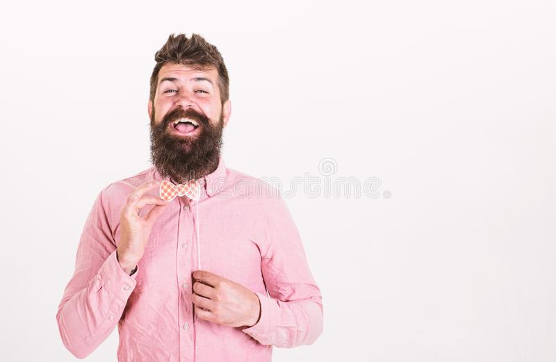 Happy smiling man with trendy beard holding paper bowtie. Bearded man having fun at birthday party, happiness concept stock images