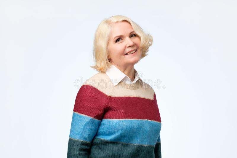 Happy smiling mature blonde woman in her sixties stock photography