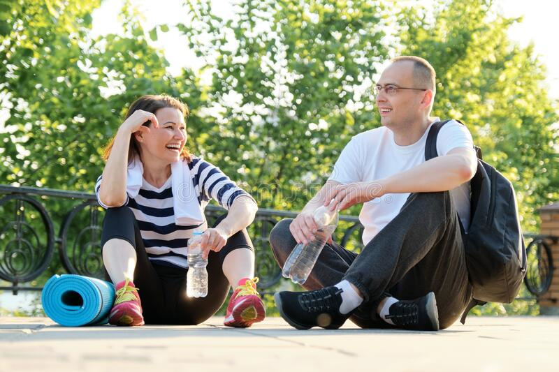Happy smiling mature couple sitting in the park, talking resting after doing sports stock photo
