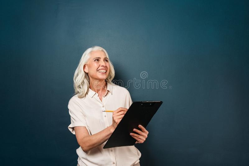 Happy smiling mature old woman writing notes in clipboard. stock photo