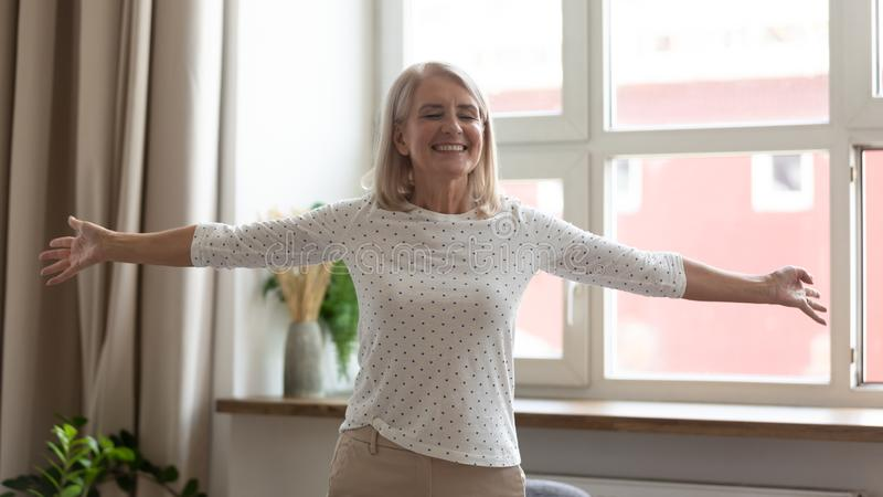 Happy mature woman standing with arms outstretched, enjoying life royalty free stock images