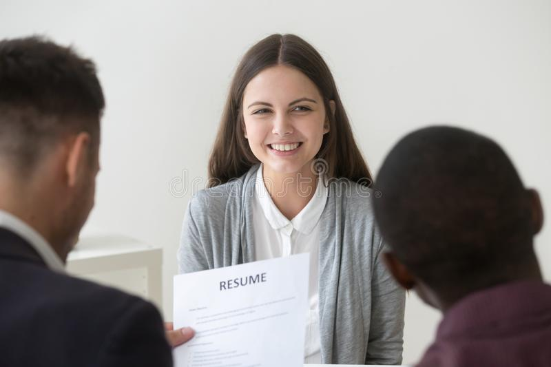 Happy smiling millennial job applicant being interviewed by hr t. Happy smiling millennial applicant being interviewed by diverse hr managers, recruiting team stock photography