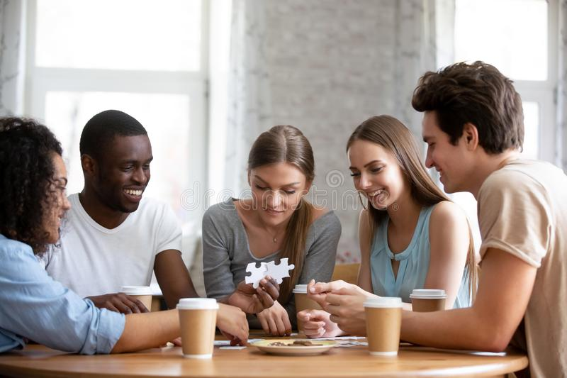 Happy smiling mixed race friends assembling puzzles brain teaser. royalty free stock photos
