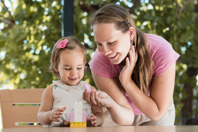Happy Smiling Mother and Baby Daughter Having Fun and Playing With Toys Outdoors stock image