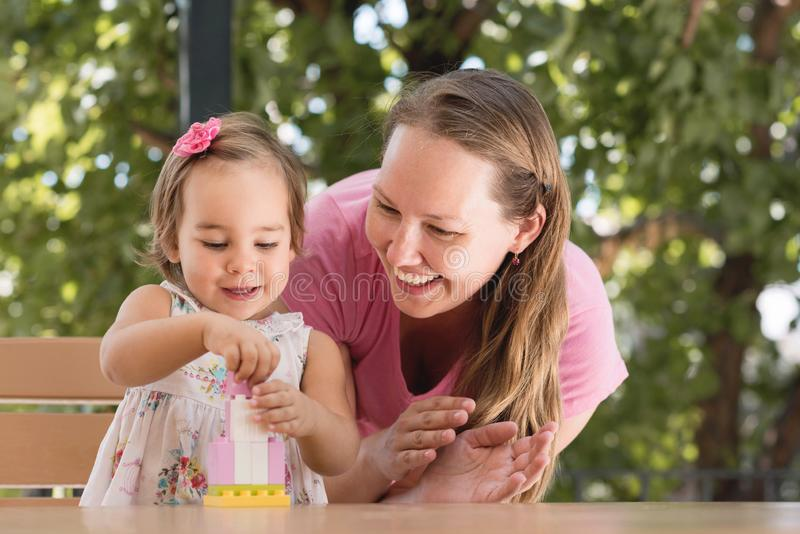 Happy Smiling Mother and Baby Daughter Having Fun and Playing With Toys Outdoors royalty free stock photo