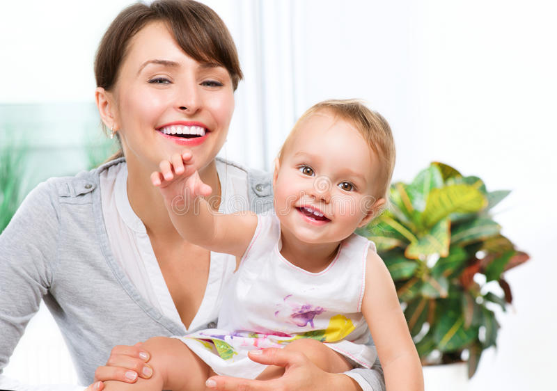 Happy Smiling Mother and Baby. Kissing and hugging at Home royalty free stock photo