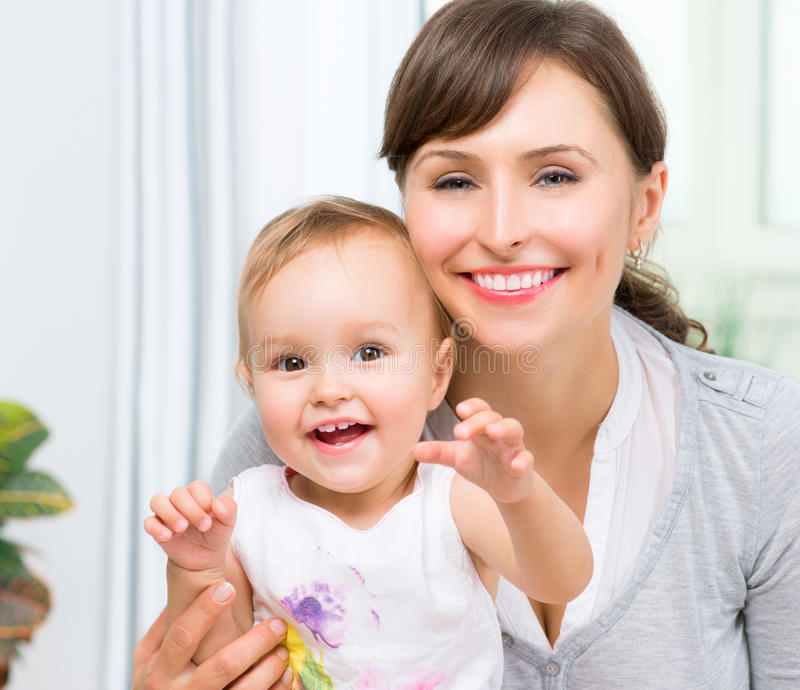 Happy Smiling Mother and Baby. Kissing and hugging at Home royalty free stock image