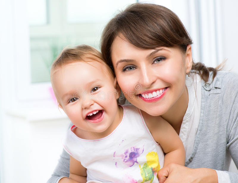 Happy Smiling Mother and Baby. Kissing and hugging at Home stock image