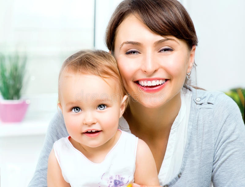 Happy Smiling Mother and Baby. Kissing and hugging at Home royalty free stock images